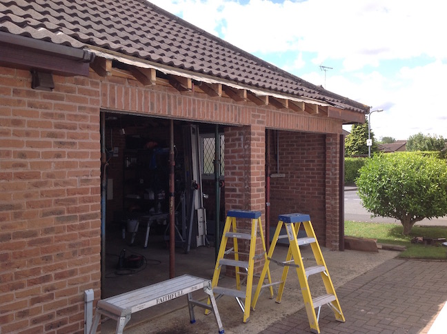 Garage doors removed and roof tiles to expose top bricks