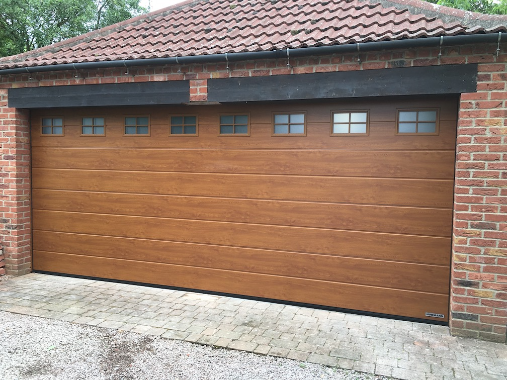 A Hörmann Sectional door M-Ribbed Golden Oak with windows